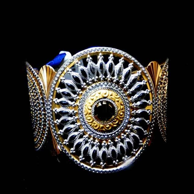 Gold Rhodium finish bangle bracelet.Approx Wt. - 60gm (22Kt). A very classical product from the house of royal creations. An openable bracelet alloy body in two flaps which merges to a floral structure on which a centre diamond is stubbed. Somewhat imparts Arabic look. Heavy piece of ornament for bigger events.  Get Latest Bracelets 100% Certified Jewellery from Jewels Box (Gold & Diamonds).  A gold bracelet is the most donned style of bracelets by men, women and kids as well. Pure indulgence in every form, a solitaire bracelet speaks of elegance